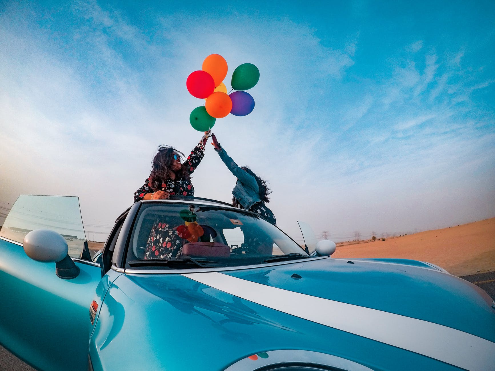two women holding assorted color balloon lot